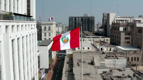 Peruvian flag waving against buildings in the historic center of Lima, the capital of Peru. Patriotism and nationalism concepts.