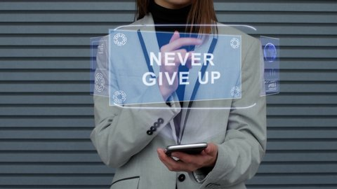 Unrecognizable business woman, interacts with a HUD hologram with text Never give up. Girl in a business suit uses the technology of the future mobile screen against the background of a striped wall