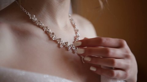 The bride hand straightens the necklace. Bride dresses a necklace.