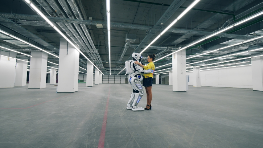 Person and cyborg meet in a room, hugging each other. | Shutterstock HD Video #1030374422