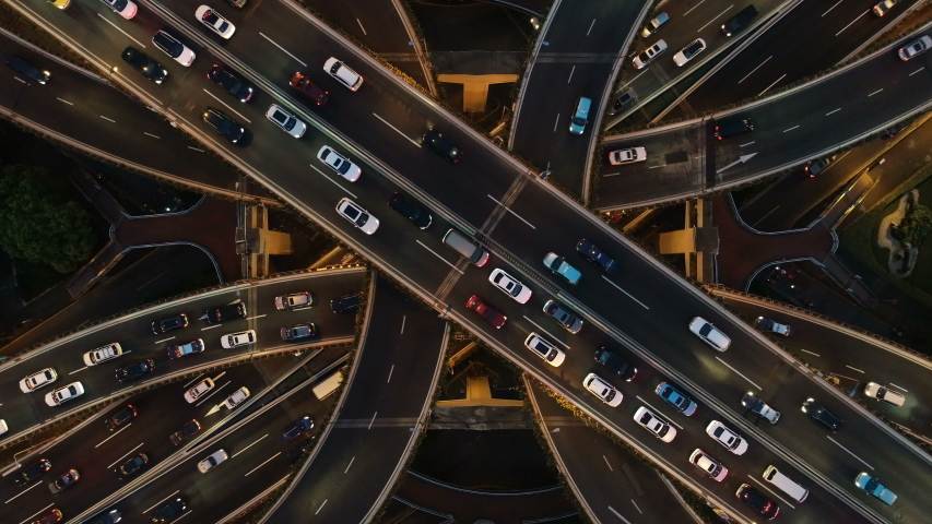 Rising drone shot reveals spectacular elevated highway and convergence of roads, bridges, viaducts in Shanghai at night, transportation and infrastructure development in urban China #1030403972