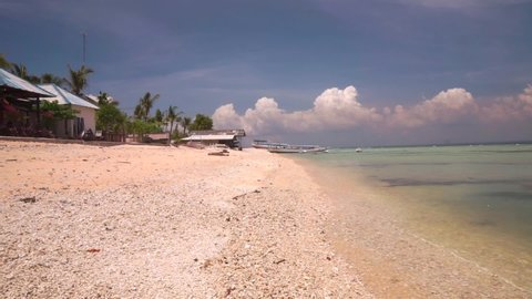 Picturesque deserted beach without people on Nusa Lembongan island. Calm sea washes sand with gentle waves of turquoise Indian Ocean. Small modest restaurants and resorts in background. 50 fps full hd