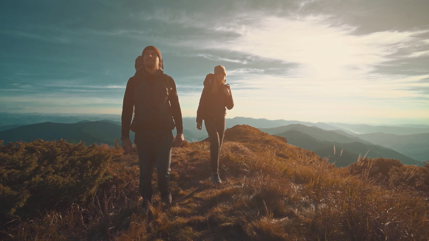 The man and woman walking along the mountain on a sunny background. slow motion   Shutterstock HD Video #1030416062