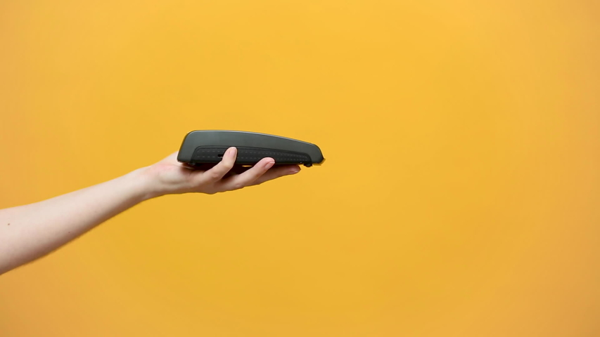 Close up cropped photo of female holding in hands wireless modern bank payment terminal to process acquire credit card payments black card isolated on yellow background. Copy space mock up advertising | Shutterstock HD Video #1030421732