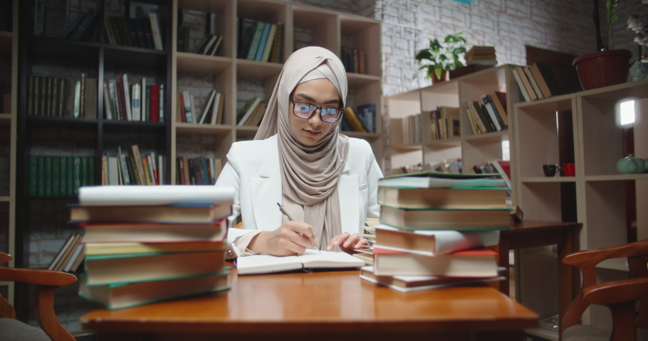 Muslim student is doing research at desk full of books in library. Girl wearing hijab is preparing for exam or making a project - student lifestyle, modern islam close up 4k | Shutterstock HD Video #1030428032