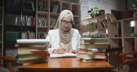 Muslim student is doing research at desk full of books in library. Girl wearing hijab is preparing for exam or making a project - student lifestyle, modern islam close up 4k