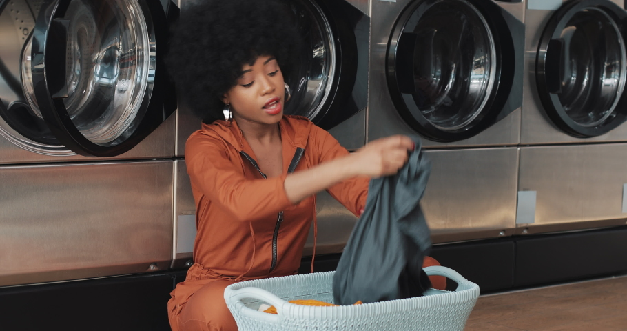 African American young woman sorting laundry in basket sorting clothes before washing sitting in the self-service public laundry. | Shutterstock HD Video #1030456862