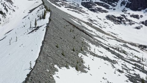 Aerial drone bird's eye view flyover shot showing a mountain covered in snow from one side at the Joffre Frozen Lake in Pemberton, British Columbia, Canada.