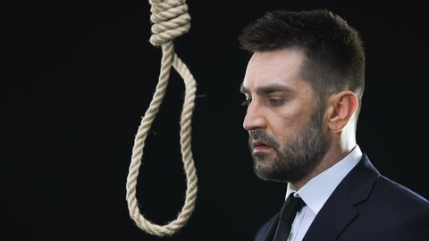Desperate business man putting hangmans noose around neck, bankruptcy, close-up