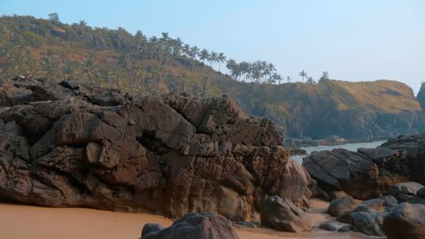 Amazing landscape - mountains overgrown with palm trees, a beautiful blue ocean and a wild beach between them, the dream of any tourist, Goa, India. Shot in motion
