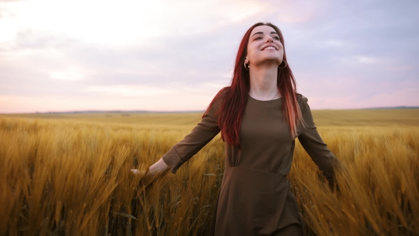 Romantic and carefree young woman in slow motion video walking on field wheat enjoying freedom and calmness on rural nature during vacations holidays. Incredible colorful sunset | Shutterstock HD Video #1030587512