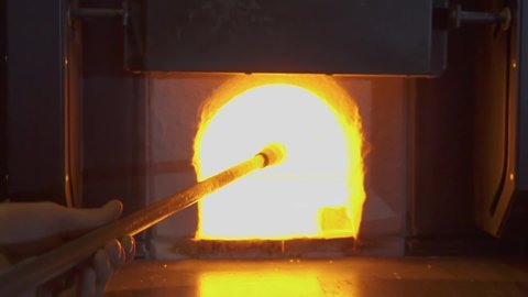 Glassblower in his workshop taking the rod with liquid glass out of glowing hot oven. Close-up.