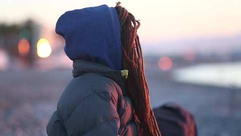 closeup cute pretty young woman with dreadlocks and in down jacket, sitting on the sea beach at sunrise and smilly looking at the camera.
