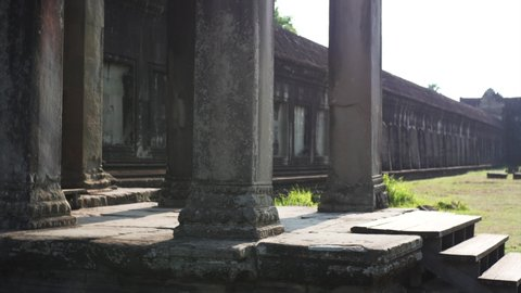 Sliding view of young woman taking photo from porch of Angkor Wat temple built in 12th century in Cambodia and dedicated to Vishnu. Cambodia