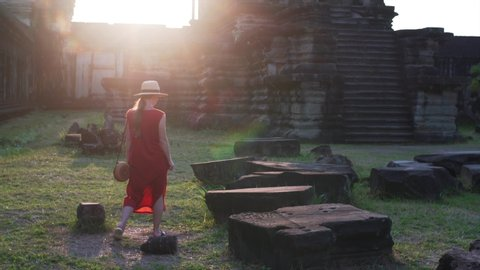 Woman in red dress is walking among ruins of Angkor Wa temple at sunset. It was built by khmer civilization in 12th century. Cambodia