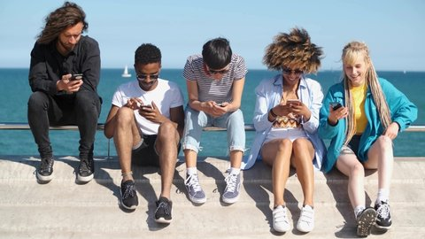 Group of trendy multiracial women and men sitting on waterfront absorbed with mobile phones spending time together in summer time