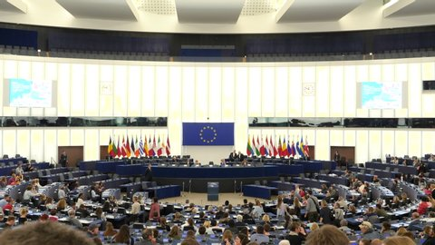 Strasbourg, France - Circa 2018: People inside hemicycle of European Parliament headquarter in Strasbourg with all Eu Members flags on the tribune and explanation about how parliament works