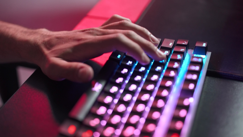 Young gamer plays a video game, close-up of hands on the keyboard, illuminated coral color and multicolor neon, cybersportsman. | Shutterstock HD Video #1030743452