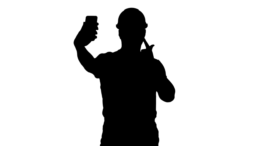 Silhouette Smiling handsome young builder making selfie with mobile phone. | Shutterstock HD Video #1030751162