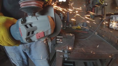 Cutting metal with orange sparks. Close-up view, slow motion. Man cuts a metal rod with circular saw in garage workshop. Worker using industrial grinder