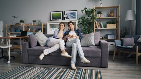Zoom in of young family man and woman watching sad movie on TV eating popcorn at home sitting on couch together. Emotional girl is holding paper tissue.
