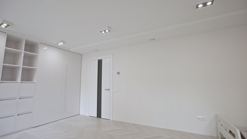 Vacant unfurnished room interior with wooden herringbone parquet floor and white walls and ceiling lit by down lights. | Shutterstock HD Video #1030806392