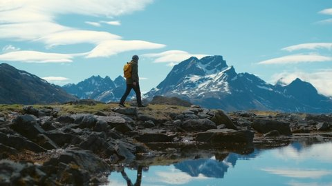 Young bearded man in a hat with a backpack comes down from the mountains on a background of snow capped mountains