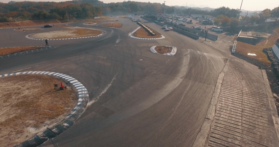 Overhead Aerial Drone Shot Over Multiple Import Race Cars as they Drift Around a Race Track in Unison.   Shutterstock HD Video #1030884182
