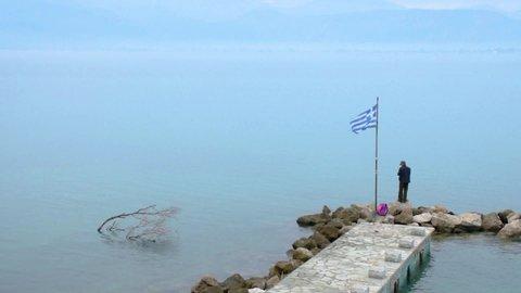 NAFPLIO, ARGOLIS / Greece - 12 04 2018: NAFPLIO, GREECE, 02 DEC 2018 : Man fishing on dock in Nafplio city, Greece