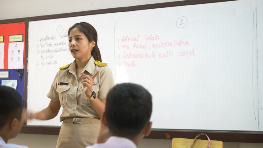 Thai high school female teachers is teaching the history of the Americas, with each group of students answering questions and writing on the whiteboard. The meaning are the name of Columbus. | Shutterstock HD Video #1030957412