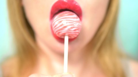 close-up, female sexy lips with red lipstick suck big pink round lollipop. copy space. blue background