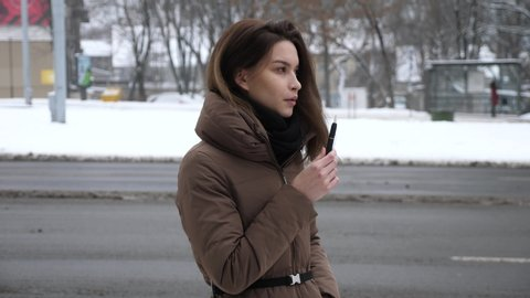 Slow motion of a beautiful brunette woman model standing outside in the cold snowy weather smoking an e cigarette inhaling and puffing out smoke with warm jacket, strong jaw line and an intense stare