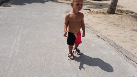 Cute two year old white boy trying to walk down the path in big female summer flip flops. beach in the background.
