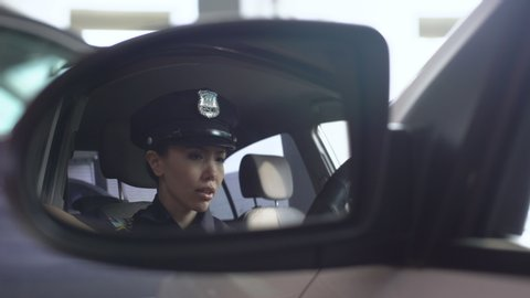 Exhausted policewoman with headache taking off service cap, massaging temples