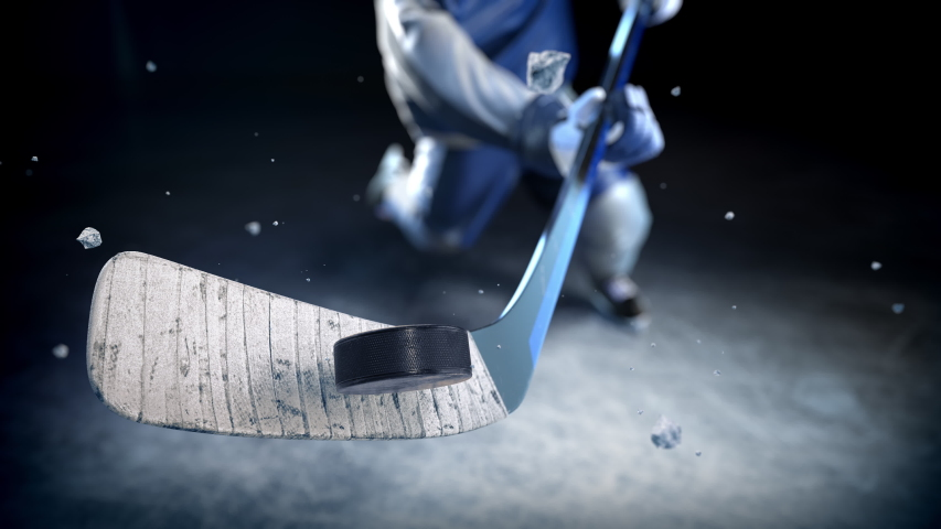 Hockey player in blue uniform hits the puck in slow motion. Excellent close-up (4k, 3840x2160, ultra high definition) | Shutterstock HD Video #1031144762
