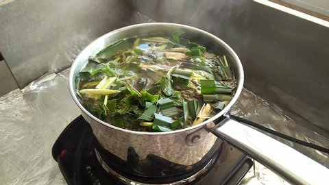 Boiling Thai herbs which are sliced lemon grass,  pandan leaves and mint leaves together with white smoke floating above the stainless steel cooking pot