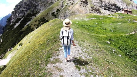 Full length view of smiling young woman wanderlust in casual wear walking on path in mountains with hairpins road view, female millennial tourist explore nature valley in alps having trekking tour