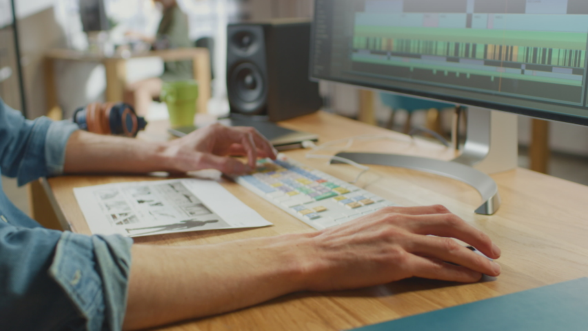 Close Up Shot of Video Editor's Hands Working with Footage on His Personal Computer with Big Display. He Works in Cool Office Loft. Laptop and Headphones Lie on the Table.