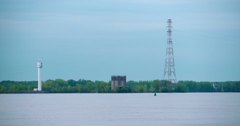 Montreal, Quebec / Canada - 06 01 2019: Ile Charon radar site of Canadian Coast Guard and ventilation tower of Louis-Hippolyte Lafontaine Bridge–Tunnel and Hydro-Quebec power lines.