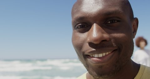 Front view of African american male volunteer looking at camera on the beach. He is smiling 4k