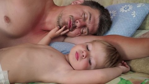 Father and son woke up early in the morning. A one-year-old blond kid of European appearance smiles and stretches next to his sleeping father. One morning in the life of father and son