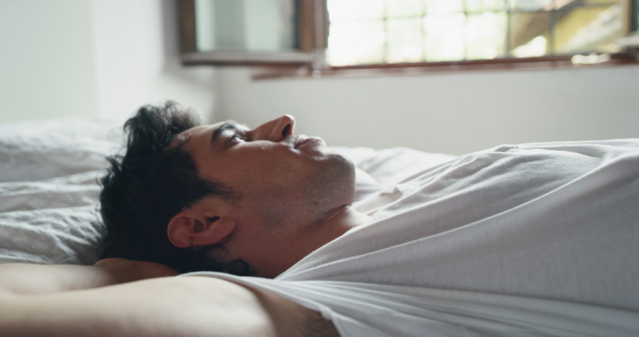 Slow motion of young handsome man is relaxing in the bedroom in the early morning in a sunny day. | Shutterstock HD Video #1031294762