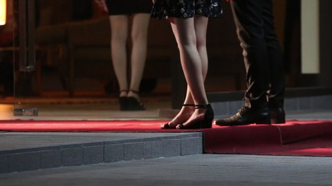 Women in long formal dresses and heels arrive at a red carpet event. Celebrities walk the red carpet. Movie stars arrive for a premier.