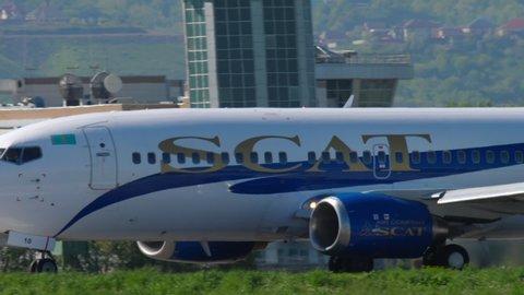 ALMATY, KAZAKHSTAN - MAY 5, 2019: SCAT Airlines Boeing 737 UP-B3710 accelerate before departure against Almaty city skyline. Almaty International Airport, Kazakhstan