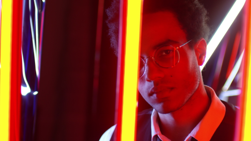 Close up of Middle Eastern man wearing round shaped spectacles standing behind red neon lights and looking at camera | Shutterstock HD Video #1031547212