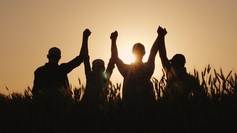 A group of successful young people hold hands, together they raise their upper hand. Successful team and team building concept.
