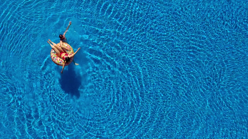 Aerial view of couple having fun in the pool, man is swimming and a woman is lying on an inflatable donut | Shutterstock HD Video #1031602052