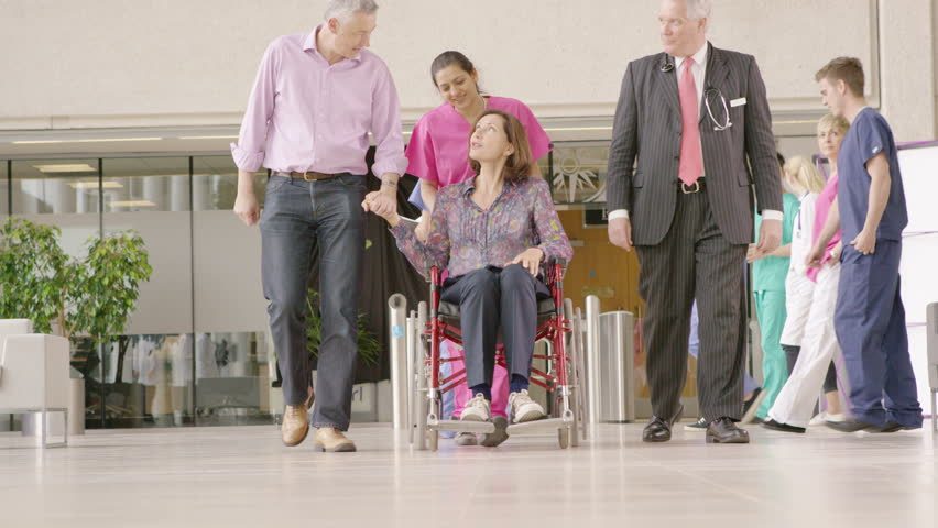 4K Caring medical staff in modern hospital help a patient in a wheelchair to stand   Shutterstock HD Video #10316252