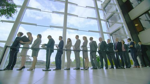 4K Diverse group of business people waiting in line in modern glass building