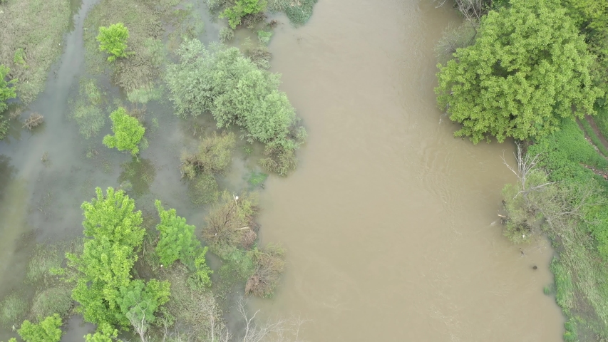 Descending over the flooded coastal area of narrow river 4K aerial video | Shutterstock HD Video #1031719292